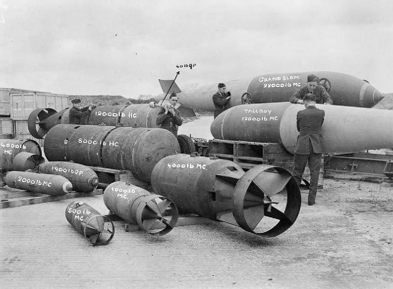 Pokazowe zdjęcie bomb używanych przez RAF podczas wojny. Po prawej za lotnikiem Tallboy. W tle Grand Slam. Po lewej przed Tallboy klasyczna bomba o podobnej masie. Widać różnicę w konstrukcji
