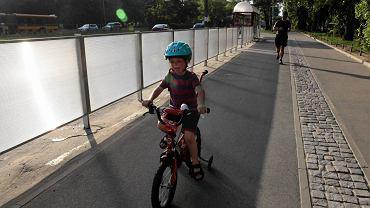 Ścieżka rowerowa wzdłuż Sobieskiego w Warszawie. Koło przystanku przy ul. św. Bonifacego wyasfaltowaną drogę dla rowerzystów oddziela płot z poliwęglanu