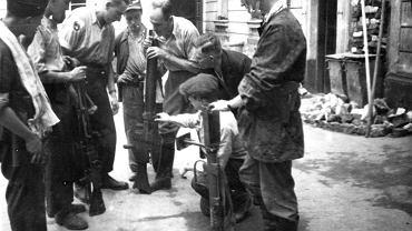 Powstańcy z bronią pochodzącą ze zrzutów na podwórzu jednej z kamienic w Śródmieściu, 23 sierpnia 1944.