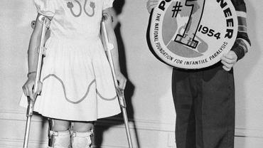 Siedmioletni Randy Kerr jako pierwsze dziecko na świecie został zaszczepiony przeciwko polio w 1954 r. Wynaleziona przez Jonasa Salka szczepionka weszła do powszechnego użycia rok później. Na zdjęciu Randy z pięcioletnią Mary Kosloski cierpiącą na choroba Heinego-Medina, którą wywołuje wirus polio. Dziewczynka zachorowała cztery lata przed wynalezieniem szczepionki. W latach 50. XX wieku choroba Heinego-Medina dotykała w USA 1 noworodka na 5 tys. noworodków. Dzięki szczepieniom dziś choroba występuje tylko w kilku krajach na świecie.