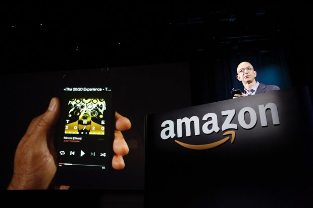 Amazon CEO Jeff Bezos shows off his company's new Fire smartphone at a news conference in Seattle, Washington June 18, 2014. Bezos unveiled a $200 smartphone called
