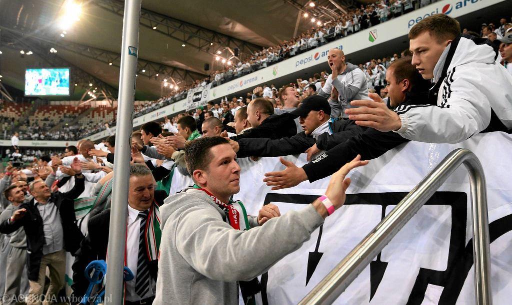 Koszykarze Legii - na pierwszym planie Paweł Podobas - po awansie do pierwszej ligi dziękowali kibicom za wsparcie podczas meczu piłkarzy na stadionie