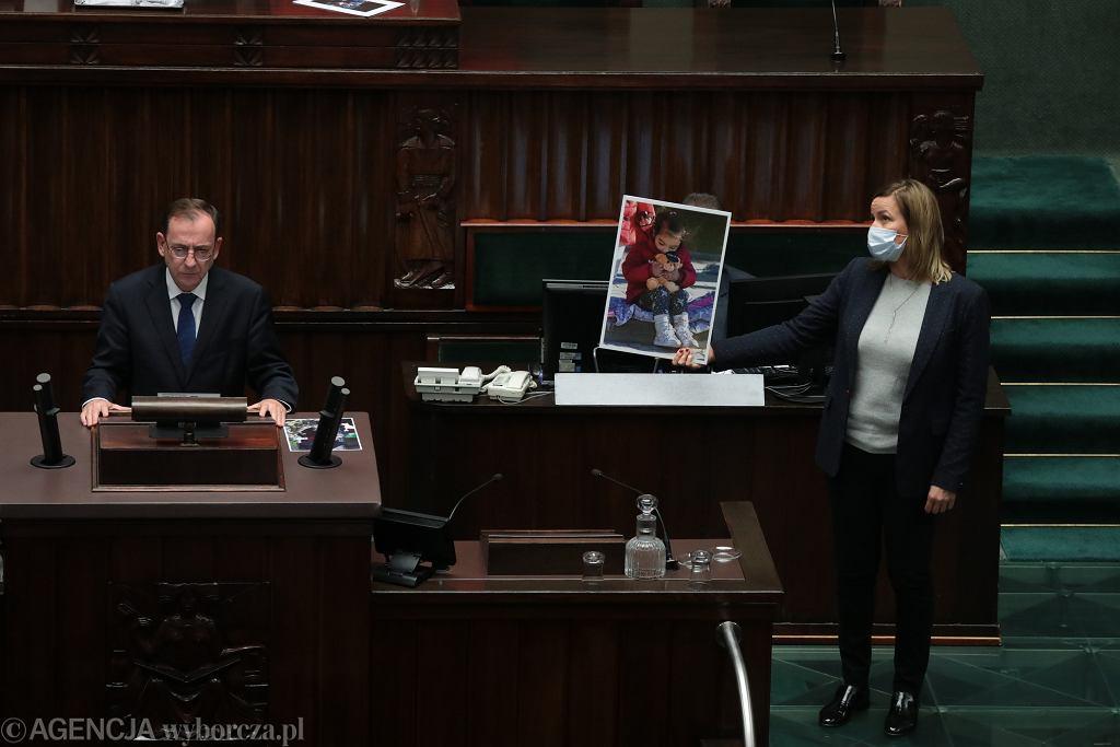 Minister spraw wewnętrznych Mariusz Kamiński i posłanka Magdalena Filiks ze zdjęciem dziecka uchodźców podczas sejmowej debaty nad przedłużeniem stanu wyjątkowego.