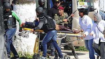 Jedna z ofiar wczorajszego ataku w Tunisie. Z tyłu autokar biura podróży Itaka