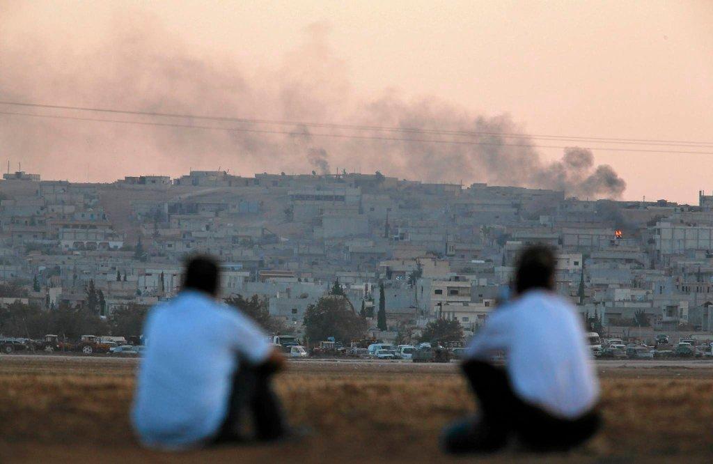 Kurdyjscy Turcy obserwują z tureckiej granicy skutki ataku lotniczego w syryjskim Kobani