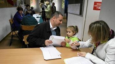 Jacek Zadrożny pokazuje córce, na czym polega głosowanie