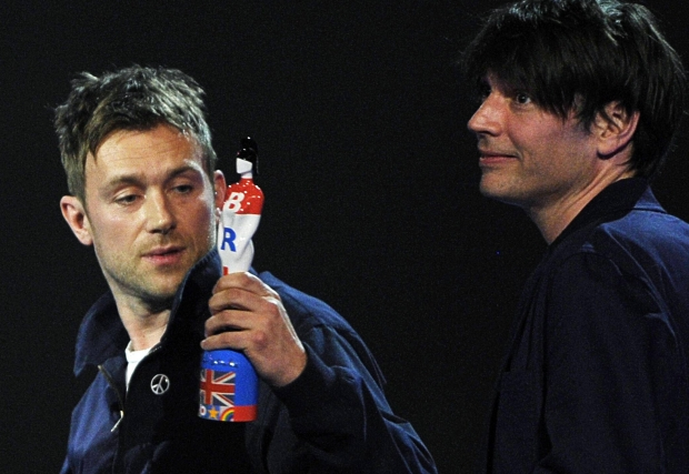 Damon Albarn (L) of Blur holds up the award for outstanding contribution during the BRIT Music Awards at the O2 Arena in London February 21, 2012.   REUTERS/Dylan Martinez (BRITAIN - Tags: ENTERTAINMENT) (BRIT-WINNERS)
