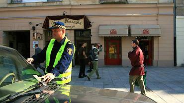 Strażnik wkłada za wycieraczkę jeden z niewielu mandatów