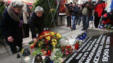 mieszkańcy Warszawy składają kwiaty pod pamiątkową tablicą