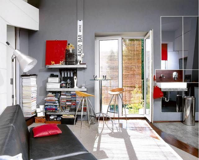 Metalowe dodatki, szkło i nowoczesne meble oswaja kilka czerwonych akcentów i wysłużona bambusowa roleta. Reszty dokonuje naturalne światło kładące się smugami na podłodze.