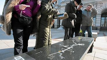 Turyści deliberują nad ławeczką Chopina przed pałacem Staszica