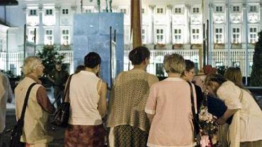 Przed krzyżem na Krakowskim Przedmieściu ludzie wciąż stawiają znicze i kładą kwiaty