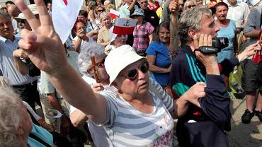 Pod Pałacem tłumy protestujących przeciwko przeniesieniu krzyża. Słychać okrzyki ''Tu jest Polska!'', śpiewane są religijne pieśni i hymn państwowy.