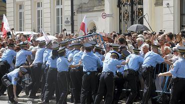 Ludzie przepychają się przez kordon policji