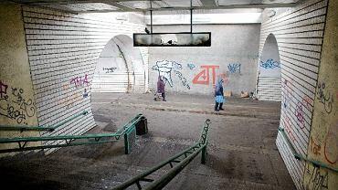 """Przejście podziemne przy dworcu PKP Stadion. W tunelu brud i bazgroły. W rozbitej gablocie, niegdyś z widocznym napisem """"Peron2"""" zagnieździły się gołębie."""