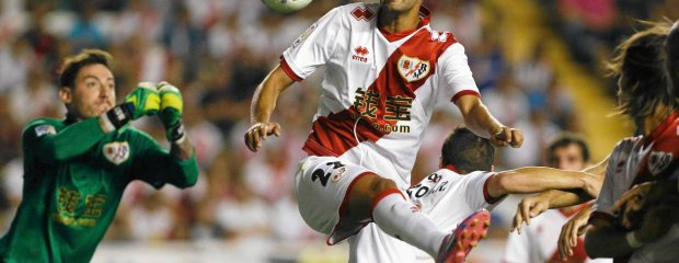 Rayo Vallecano's Alberto Bueno jumps for the ball during their Spanish first division soccer match against Atletico Madrid at Vallecas stadium in Madrid August 25, 2014. REUTERS/Juan Medina (SPAIN - Tags: SPORT SOCCER) SLOWA KLUCZOWE: :rel:d:bm:GF2EA8P1LYJ01