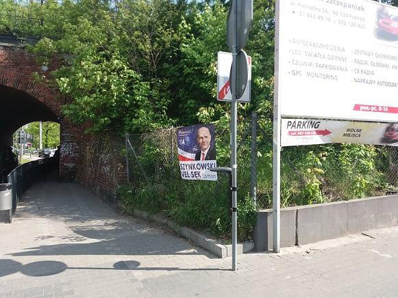 Plakat kandydata PiS Szymona Szynkowskiego vel Sęka wisi na płocie przy Kościelnej bez pozwolenia