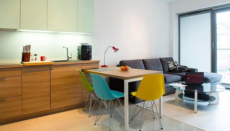 Strefy kuchenną i wypoczynkową rozgranicza stół.