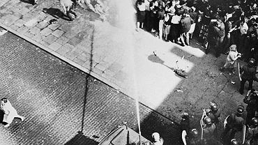 3 maja 1983 r., kościół św. Jana Chrzciciela przy ul. Świętojańskiej w Warszawie. Zmotoryzowane Odwody Milicji Obywatelskiej przy pomocy opancerzonego pojazdu wyposażonego w sikawkę tryskającą wodą pod dużym ciśnieniem pacyfikują demonstrację poparcia dla zdelegalizowanej 'Solidarności' zwołaną z okazji 192. rocznicy uchwalenia Konstytucji 3 maja.
