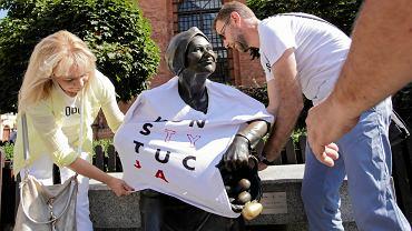 Akcja KOD w Toruniu. Zakładanie koszulek z napisem ' KONSTYTUCJA' na pomniki
