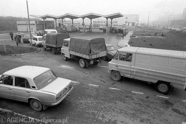 Rok 1989. Kolejka na stacji benzynowej. Na początku lat 80. zaczęto wprowadzać tankowanie w dni parzyste i nieparzyste w zależności od ostatniej cyfry numeru rejestracyjnego. Potem wprowadzono dodatkowe sankcje - ograniczona ilość benzyny w podczas jednego tankowania - zakazano też nalewania paliwa do kanistrów. Od września do grudnia 1981 roku dostawy benzyny do stacji CPN były już rzadkie i nieregularne - trzeba było mieć dużo szczęścia, żeby cokolwiek zatankować. Po 13 grudnia 1981 roku w ogóle zawieszono sprzedaż benzyny klientom prywatnym. Wiosną już można było tankować - ale trzy razy w miesiącu, w dni kończące się na ostatnią cyfrę rejestracji pojazdu. I tak np. właściciel auta o rejestracji GDA 5964 mógł napełnić bak 4, 14 i 24. Jednak nie do końca - samochody z silnikiem o pojemności do 900 cm sześc. mogły nabrać 10 litrów, powyżej 900 - 15 litrów, do pełna tankowały tylko motocykle. Z czasem limity podwyższono, by w końcu wprowadzić kartki na benzynę. Reglamentację zniesiono 1 stycznia 1989 roku, jednak na początku wiosny brak ograniczeń dał o sobie znać i paliwa brakowało na stacjach praktycznie na okrągło. Sytuacja unormowała się dopiero na początku lat 90