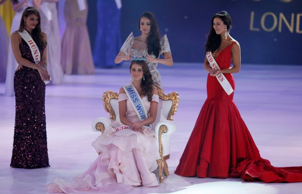 Miss South Africa Rolene Strauss is crowned Miss World 2014 by last year's winner Megan Young, at the end of the competition at the ExCel centre in London, Sunday, Dec. 14 2014. Miss Hungary Edina Kulcsar, left, was second with Miss United States, Elizabeth Safrit finishing third. (AP Photo/Alastair Grant)