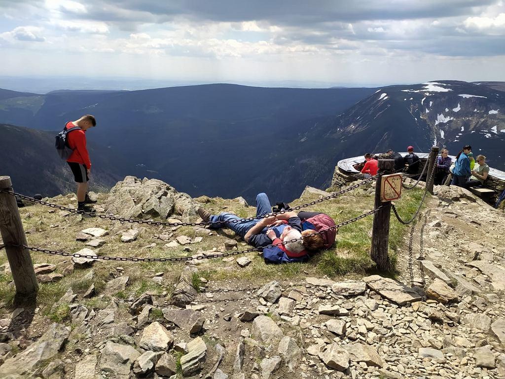 Turyści nic sobie nie robią z łańcuchów ograniczających wejście na trawę