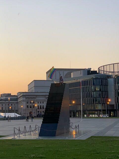 Osoba z tęczową flagą na Pomniku Ofiar Tragedii Smoleńskiej