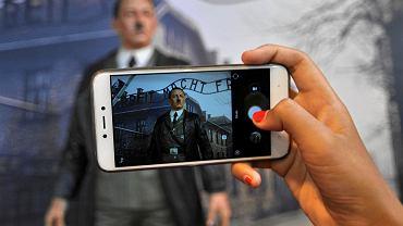 Odwiedzający muzeum robi zdjęcie woskowej postaci Adolfa Hitlera na tle zdjęcia Auschwitz. Po prawej postać z Dartha Vadera z 'Gwiezdnych Wojen'