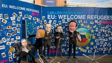 Aktorzy w maskach polityków: premier Węgier Viktor Orbán blokuje drzwi otwierane przez kanclerz Angelę Merkel; obok prezydent Francji François Hollande, premier Hiszpanii Mariano Rajoy i Wlk. Brytanii David Cameron. W tle obraz przedstawiający Aylana Kurdiego, trzyletniego chłopca, który zginął podczas przeprawy uchodźców  u brzegów Turcji