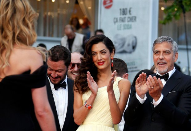 Cast member George Clooney and his wife Amal applaud actress Julia Roberts (L) as she on the red carpet as they arrive for the screening of the film