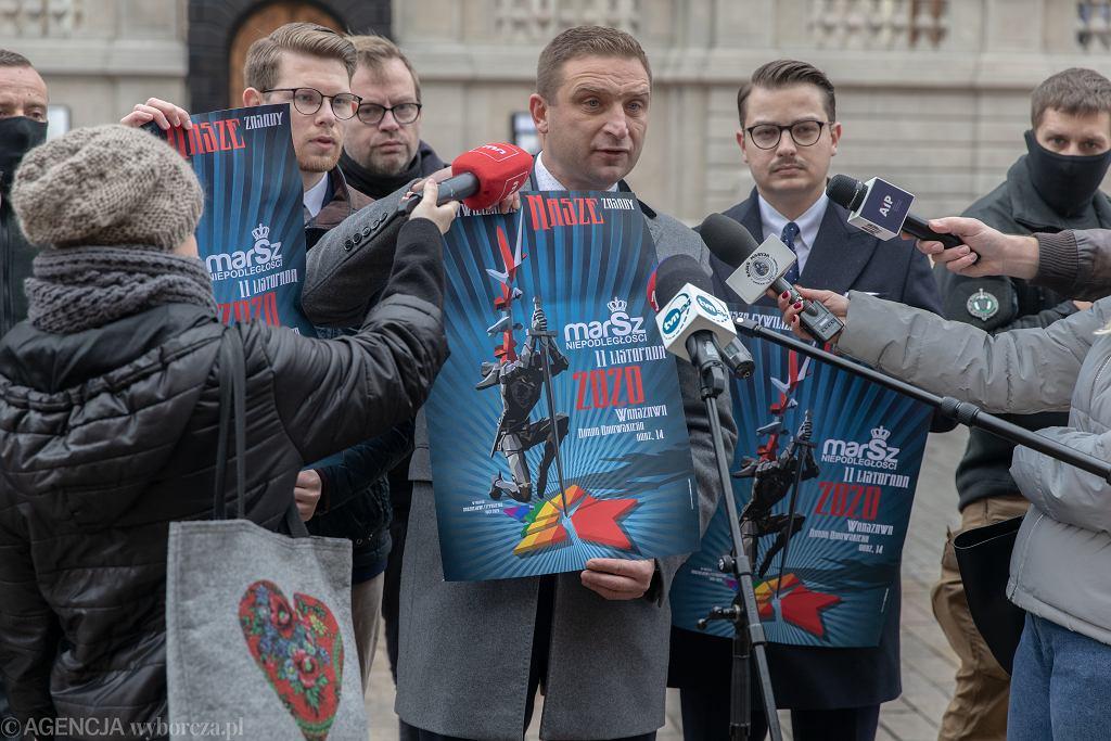 Listopad 2020 r. Robert Bąkiewicz, szef Marszu Niepodległości, prezentuje plakat tegorocznej imprezy