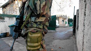 Uzbrojony żołnierz pilnuje wejścia do szkoły żydowskiej w okolicy której doszło do ataku na nauczyciela. Mężczyzna przez ciosami maczetą obronił się Torą