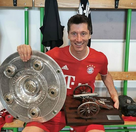 Robert Lewandowski z mistrzowską paterą i armatą, zdobytymi w Bundeslidze 2019/20
