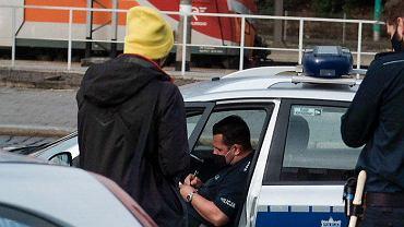 Policjanci przy dworcu Poznań Główny zatrzymują chłopaka bez maseczki i dają mu mandat