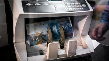 Plik franków szwajcarskich w maszynie liczącej banknoty.