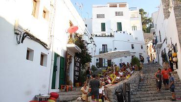 Ludzie przesiadają na schodach przy jednej z knajpek na starym mieście