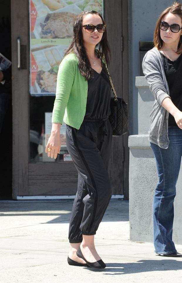 EXCLUSIVE: Christina Ricci stepped out in a shiny black jumpsuit as she left a hotel in West Hollywood, CA. The actress completed her outfit with a green cardigan, flat shoes and a leather handbag. She left the 'Palihouse' with a friend and was deep in conversation as she walked back to her car.  Pictured: Christina Ricci  Ref: SPL180005  130510   EXCLUSIVE Picture by: Whittle / Splash News