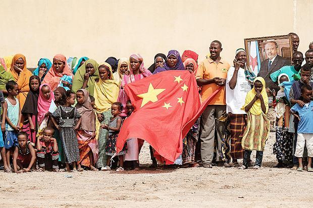 Przyszli mieszkańcy nowego osiedla w Dżibuti trzymają chińską flagę narodową i portret prezydenta Dżibuti Ismaila Omara Guellehasa, projekt jest wspierany finansowo przez chińską firmę China Merchants, 4 lipca 2018 r.