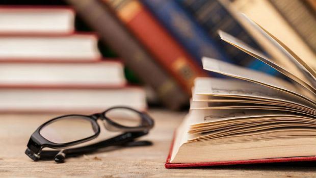 Książki w bibliotece i okulary na stole