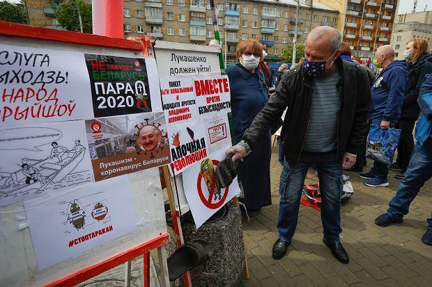 24.05.2020, Mińsk, kolejka chętnych do podpisania się na listach wspierających opozycyjnych kandydatów na prezydenta Białorusi. Jakiś mężczyzna uderza butem w wyborczy plakat Łukaszenki