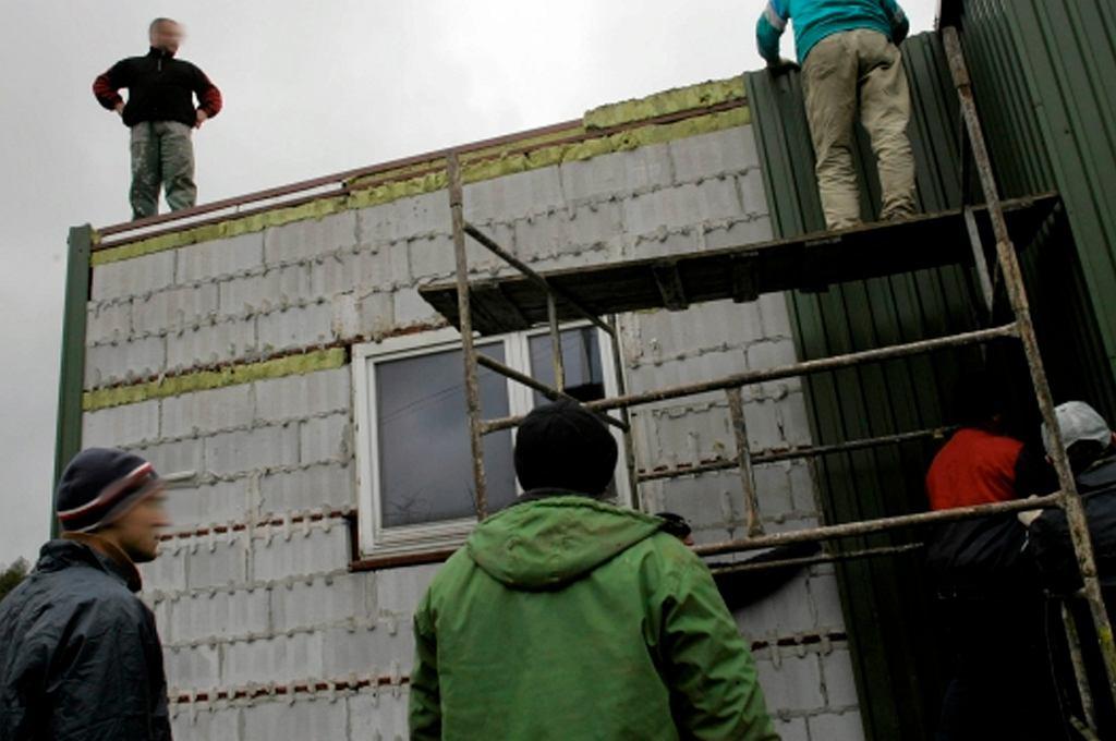 Inspektorzy nadzoru budowlanego zrywają blachę z nielegalnie postawionego budynku