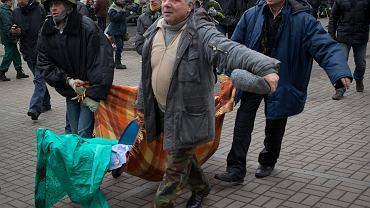 Demonstranci niosą ciało kolegi zabitego przez członków sił milicyjnych