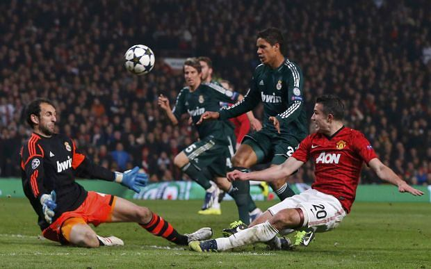 Manchester United's Robin van Persie (R) tries a shot against Real Madrid's goalkeeper Diego Lopez (L) during their Champions League soccer match at Old Trafford in Manchester, March 5, 2013.  REUTERS/Phil Noble (BRITAIN  - Tags: SPORT SOCCER)
