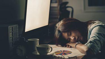 Chińska pracownica biurowa ucina sobie drzemkę przy biurku.