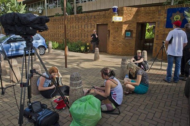 Journalists camp outside the police station in Brooklyn, east of Pretoria, Monday, Feb. 18, 2013 where athlete, Oscar Pistorius spent a fifth day in custody charged with the shooting death of his girlfriend Reeva Steenkamp. Pistorius faces a bail hearing in court tomorrow on the same day that Steenkamp is to be cremated in her home town Port Elizabeth on the east coast. (AP Photo)