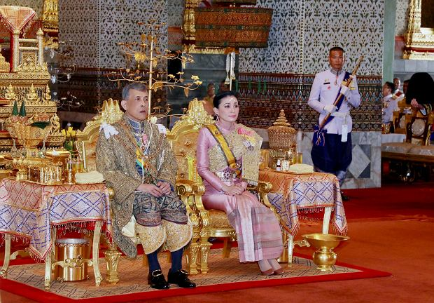 In this photo released by Bureau of the Royal Household, Thailand's King Maha Vajiralongkorn sits on the throne next to Queen Suthida as he is officially crowned king at the Grand Palace, Saturday, May 4, 2019, in Bangkok, Thailand. Saturday began three days of elaborate centuries-old ceremonies for the formal coronation of Vajiralongkorn, who has been on the throne for more than two years following the death of his father, King Bhumibol Adulyadej, who died in October 2016 after seven decades on the throne. (Bureau of the Royal Household via AP)
