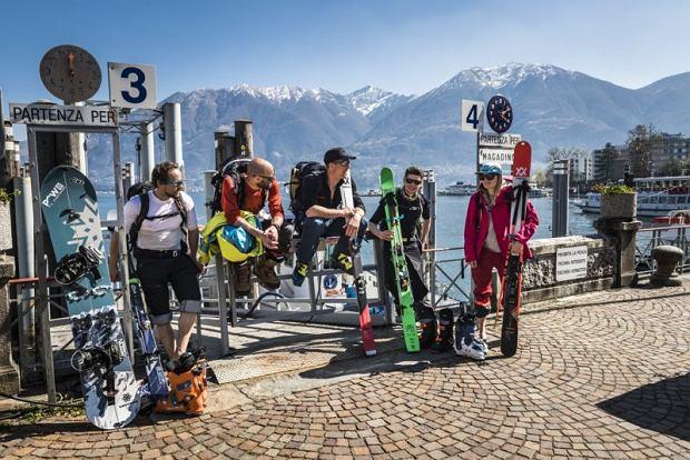 Wintermagazin Titelgeschichte Nord-Sued Winter 2019-20. Eine Gruppe Skitourengeher rastet vor dem Fruehlingshaften Lago Maggiore.
