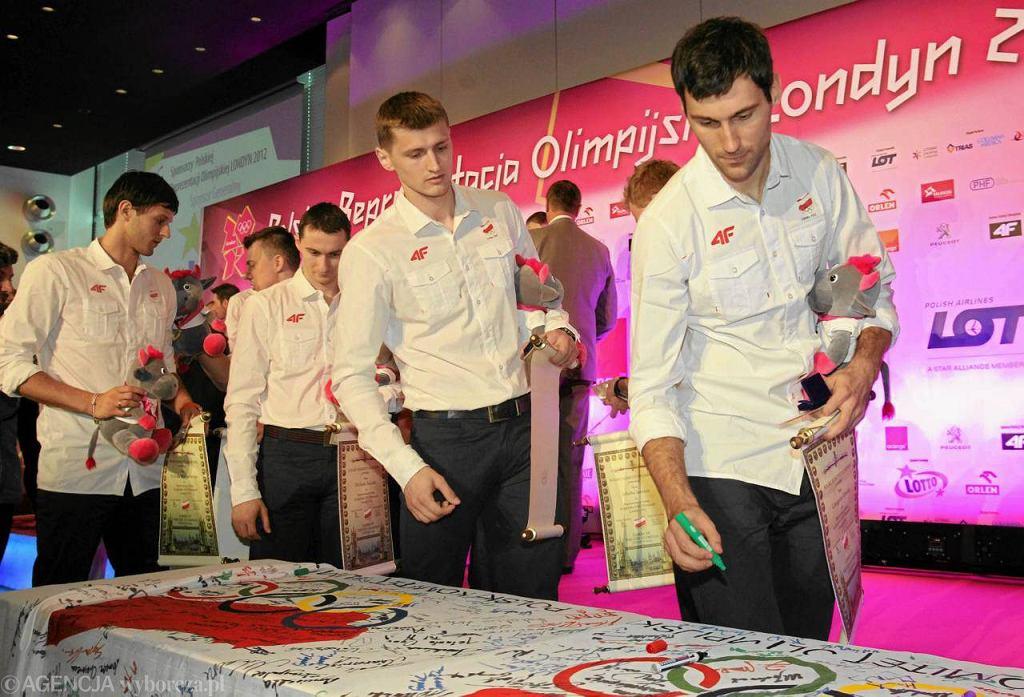 Podpisy na olimpijskiej fladze składają Grzegorz Kosok (pierwszy z prawej) i Piotr Nowakowski (drugi z prawej)