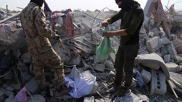 Ludzie przeszukują ruiny domu w pobliżu miejsca, w którym wysadził się Abu Bakr al-Baghdadi